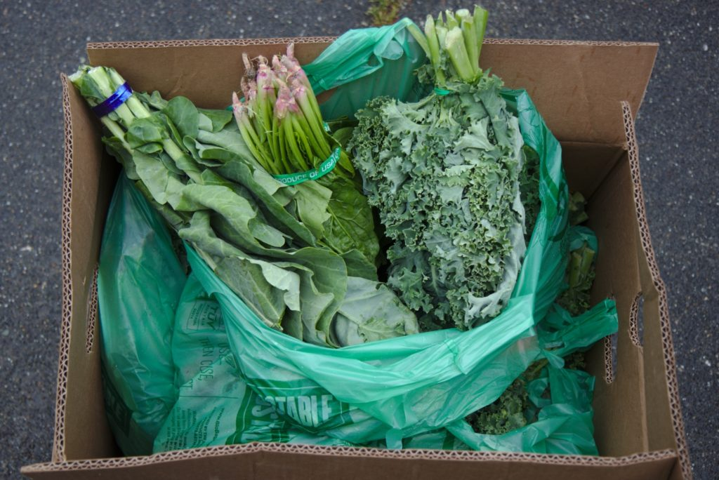 Spinach, kale, and collard greens packed in a plastic bag inside a cardboard box